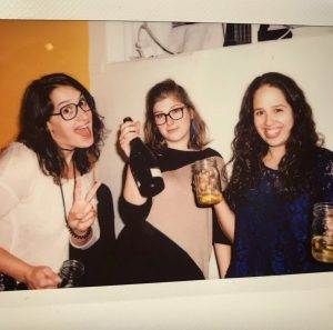 A Polaroid picture of Rachel Waxman, Rae Abramowitz, and Danielle Selber drinking champagne