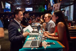 Two Jewish professionals stand behind a table and speak to a young professional who is inquiring about their organization. The table is full of swag and a laptop for email listserve sign-ups