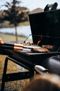 A lit grill in a park with juicy burgers cooking over the fire