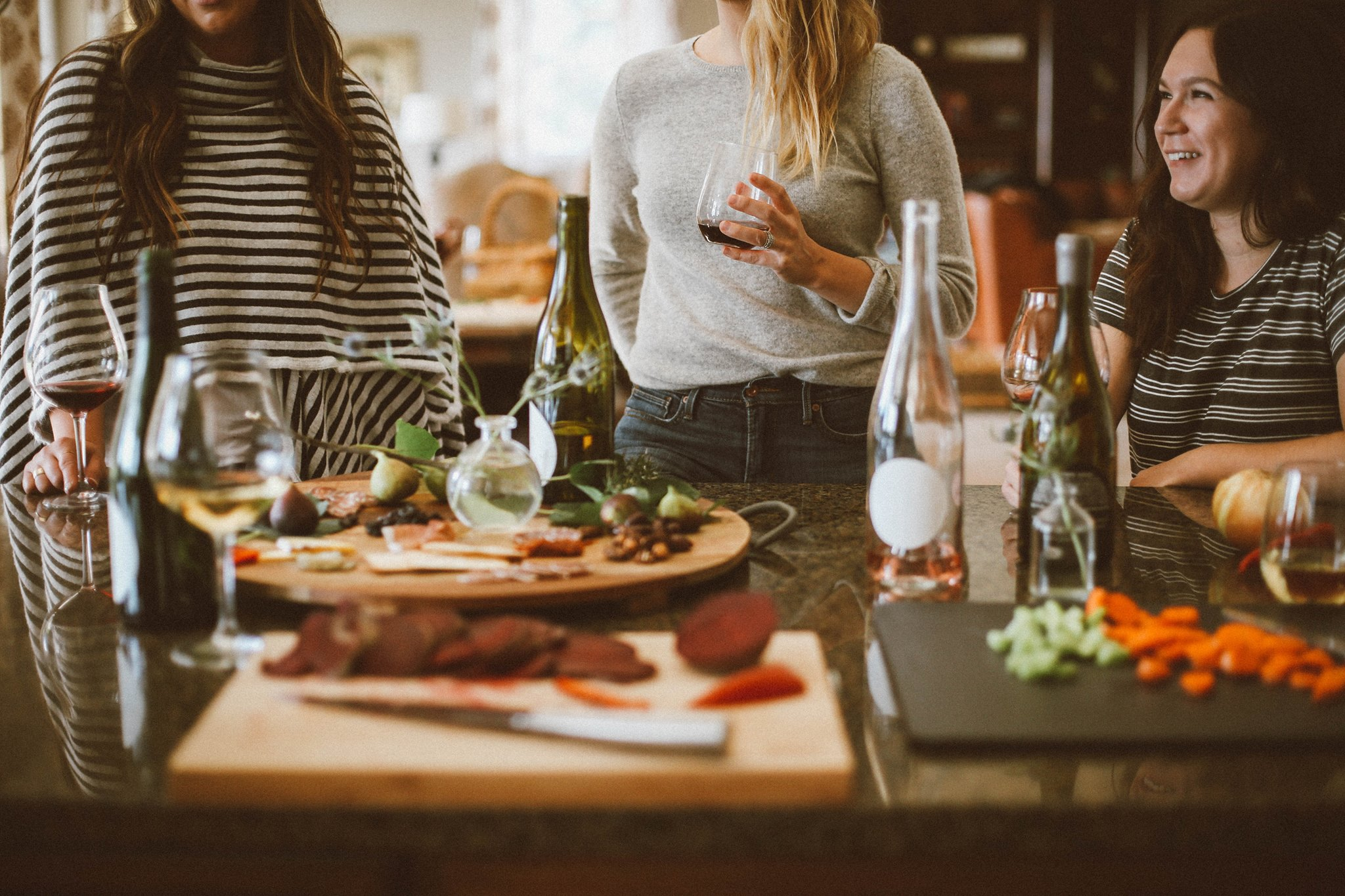 Jewish young professionals sit around a Shabbat dinner table with wine