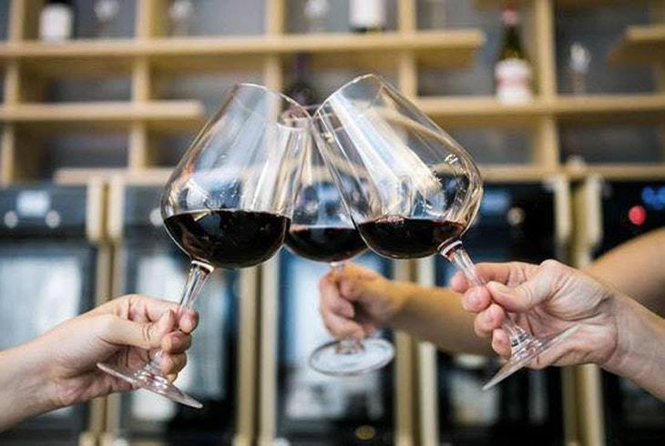 Three hands clink together three wine glasses at a wine tasting event