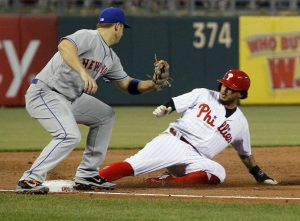 Phillies player sliding into first base while a Mets player tries to get him out