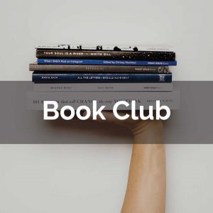 """Someone holds up a stack of six books in front of a white wall. The words """"Book Club"""" are overlaid"""