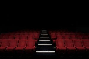 A dark, empty theater with red velvet chairs and an aisle of stairs down the middle