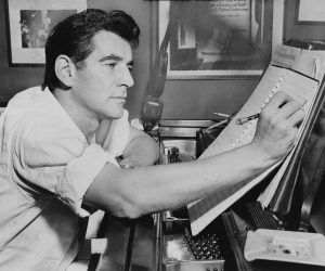 A black and white photo of a young Leonard Bernstein (photo was taken in 1985) sitting at a piano and working on a composition