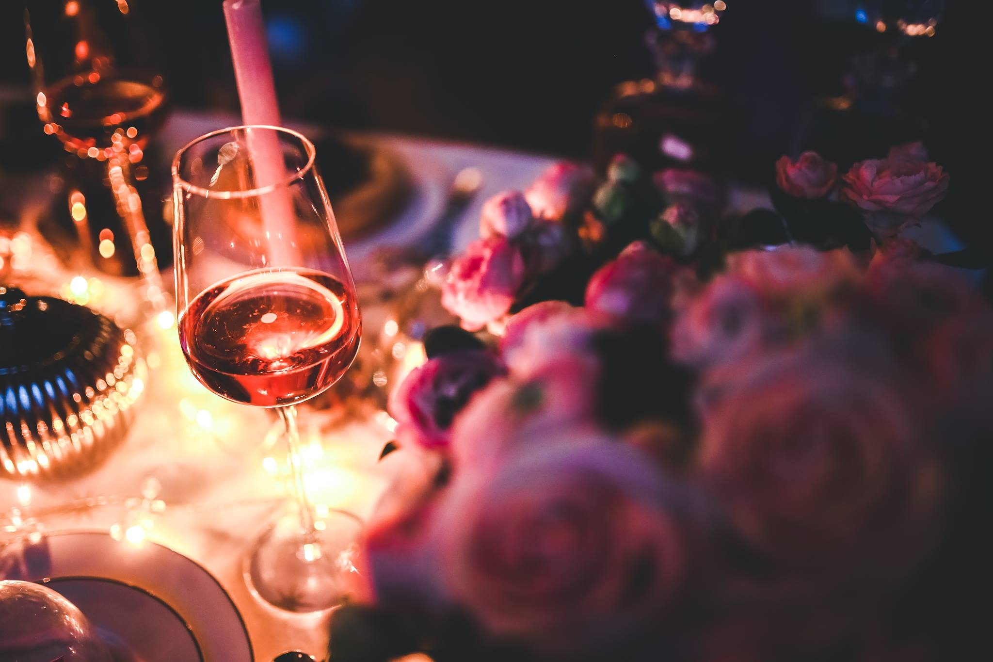 A wine glass sits on an elegantly decorated table, bathed in warm light