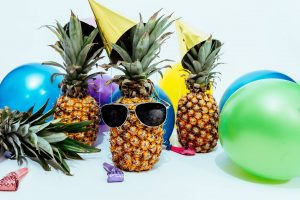 Pineapples wearing sunglasses and party hats scattered among a display of balloons and confetti