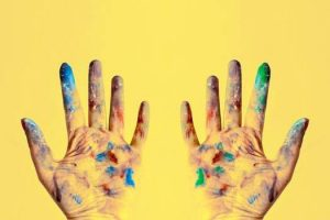 Someone is holding up their hands, which are full of colorful paint, in front of a yellow wall