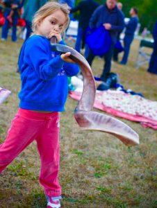 A child blows the shofar in the grass