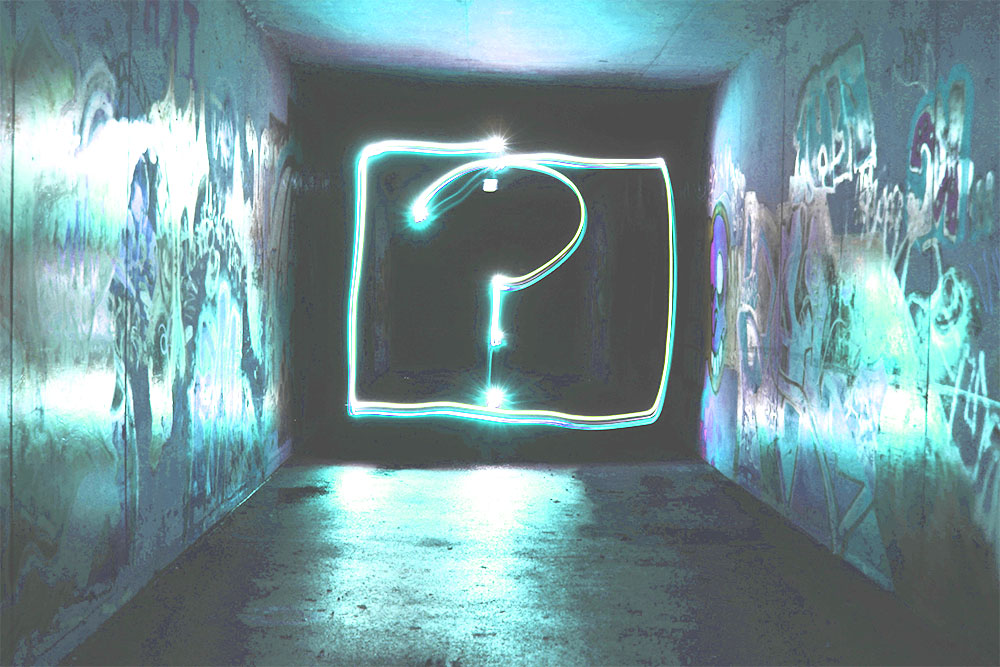 A bright blue question mark on the wall of a dark tunnel