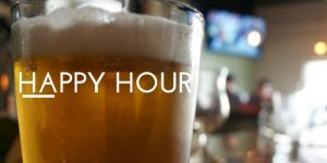 """Beer glass in the foregroud with a blurry bar in the background and the words """"Happy Hour"""" overlaid"""