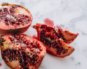 Pomegranates are sliced in half, in quarters, and in eights and displayed on a marble countertop