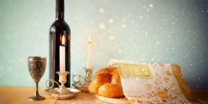 Wine glass, wine bottle, two lit Shabbat candles, and a challah sit on a wooden table