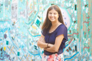 Young professional poses in front of a mosaic wall