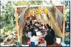 people sitting in sukkah