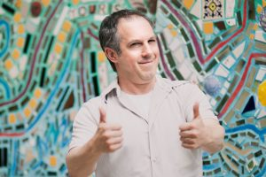 Guy giving two thumbs up in front of a mosaic