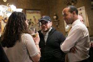 Three young professionals chat in a group at a First Thursday Happy Hour event