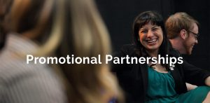 Young professional smiles at her peer while speaking at an event - Promotional Partnerships