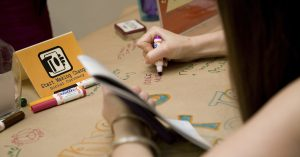 Young professional draws her ideas with marker on butcher paper