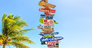 travel sign post next to a palm tree points toward all different countries