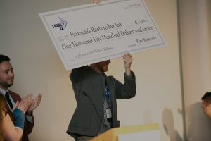 Tribe 12 fellowship alumni holds up a giant check he received from our giving circle