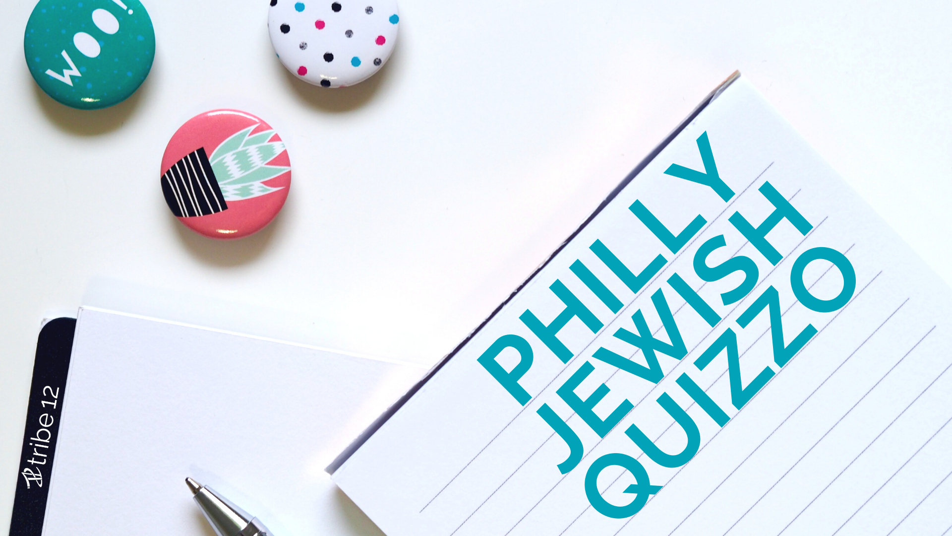 Philly Jewish Quizzo written on a notepad with a smaller notepad with Tribe 12 written on it and three colorful buttons scattered nearby as if on a desk