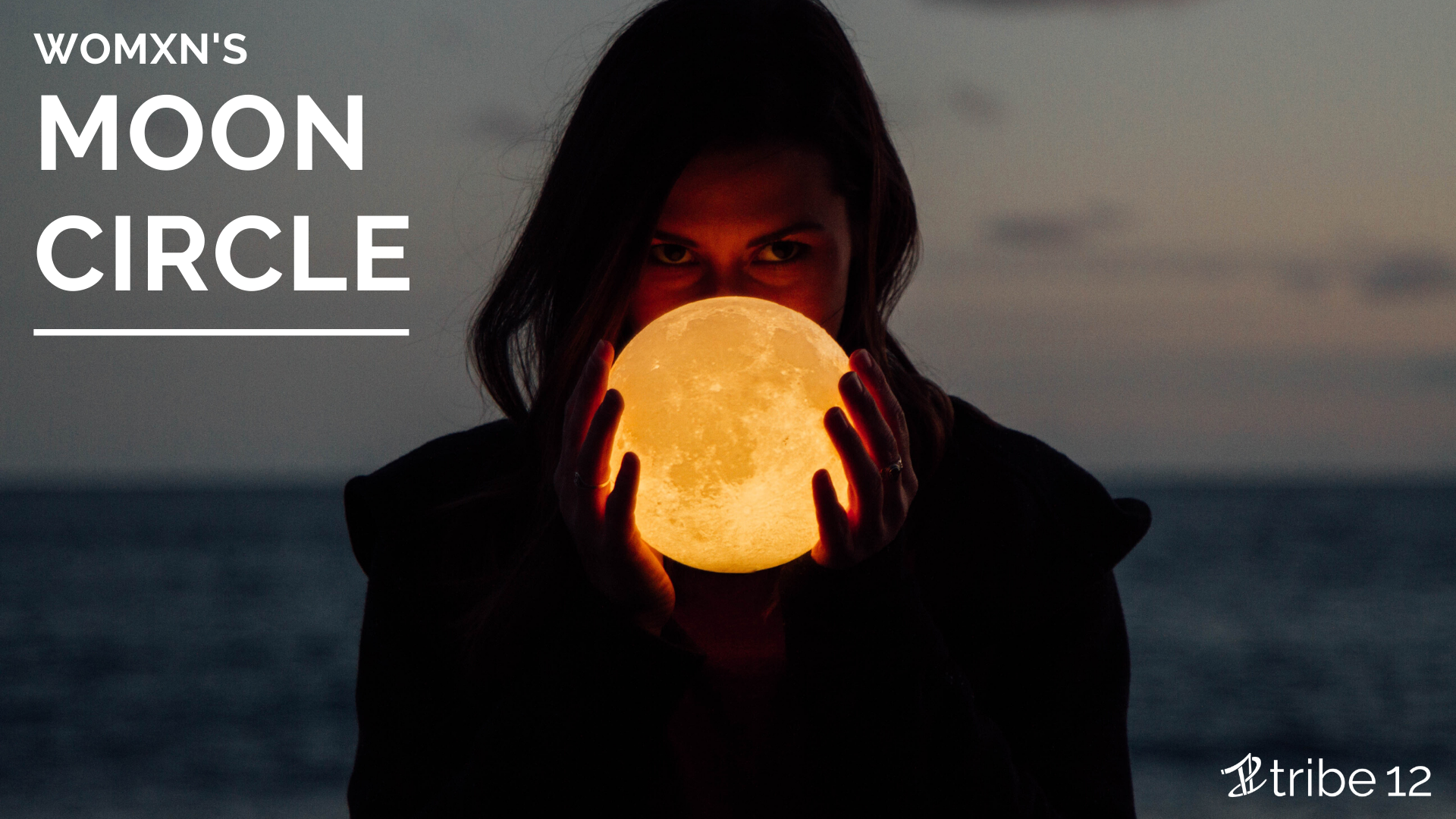 womxn's moon circle written over a photo of a woman holding a lit moon